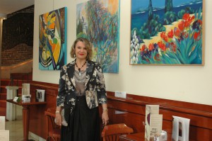 La pittrice Michèle Padoy davanti ad alcune sue opere